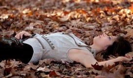 Милая женщина лежа на листьях Стоковые Фото
