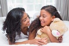 Милая женщина лежа на кровати при ее дочь усмехаясь на одине другого Стоковые Изображения