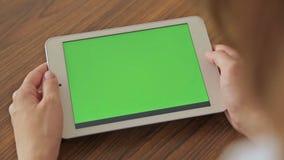 Милая женщина держа в таблетке руки с зеленым экранным дисплеем акции видеоматериалы