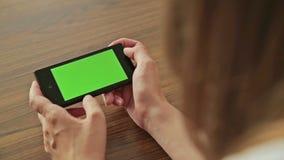 Милая женщина держа в телефоне руки умном с зеленым экранным дисплеем сток-видео
