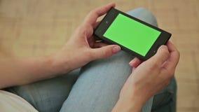 Милая женщина держа в телефоне руки умном с зеленым экранным дисплеем видеоматериал