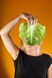 Милая женщина держа капусту как маска Стоковая Фотография