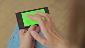 Милая женщина держа умный телефон с зелеными экранным дисплеем и касаться сток-видео