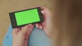 Милая женщина держа умный телефон с зелеными экранным дисплеем и перечислять видеоматериал