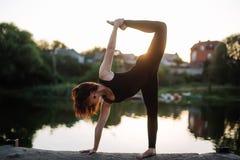 Милая женщина делая йогу работает в парке стоковое изображение rf