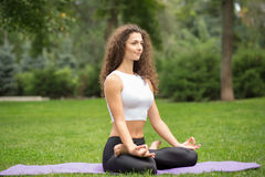 Милая женщина делая раздумье йоги в лотосе Стоковые Изображения RF