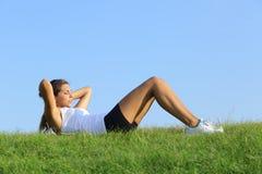 Милая женщина делая хрусты на зеленой траве Стоковые Фотографии RF