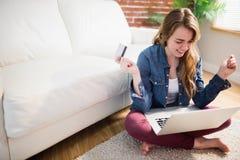 Милая женщина используя ее кредитную карточку для того чтобы купить онлайн Стоковая Фотография