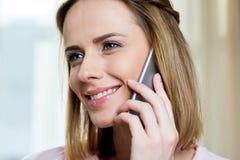 Милая женщина используя smartphone дома Стоковая Фотография RF