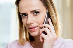 Милая женщина используя smartphone дома Стоковое Изображение