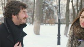 Милая женщина и милый человек враждуют в снежном парке зимы акции видеоматериалы