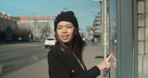 Милая женщина на автобусной остановке проверяя расписание акции видеоматериалы