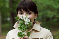 Милая женщина пахнет цветками в парке Стоковые Изображения RF