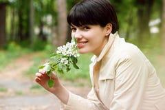 Милая женщина пахнет цветками в парке Стоковое Изображение