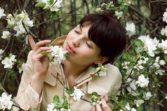 Милая женщина пахнет цветками в парке Стоковая Фотография