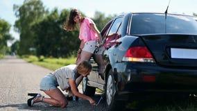 Милая женщина поднимая домкратом вверх по ее автомобилю для того чтобы изменить спущенную шину акции видеоматериалы