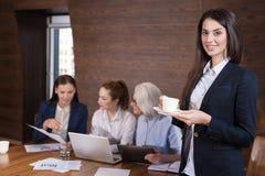 Милая женщина представляя в офисе с коллегами Стоковые Фотографии RF
