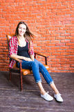 Милая женщина при длинные ноги сидя в кресле за кирпичной стеной Стоковая Фотография