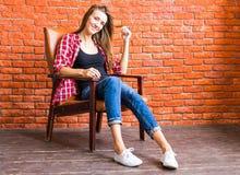 Милая женщина при длинные ноги сидя в кресле за кирпичной стеной Стоковые Изображения RF