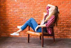 Милая женщина при длинные ноги сидя в кресле за кирпичной стеной Стоковая Фотография RF