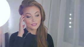 Милая женщина при элегантный стиль причёсок смотря ее отражение в зеркале акции видеоматериалы