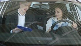 Милая женщина сидя в автомобиле и слушая к продавцу в центре автомобиля замедленные движения стоковая фотография