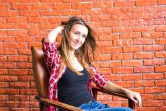 Милая женщина сидя в кресле за кирпичной стеной Стоковое Фото