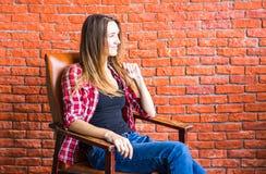 Милая женщина сидя в кресле за кирпичной стеной Стоковое Изображение RF