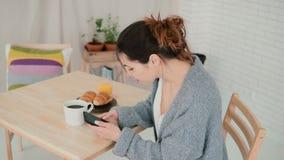 Милая женщина сидя в пижамах кухни нося и занимаясь серфингом интернет Девушка брюнет использует smartphone во время завтрака Стоковое Изображение