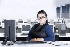 Милая женщина сидя на офисе с компьтер-книжкой Стоковое Фото