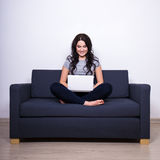 Милая женщина сидя на софе и используя компьтер-книжку дома Стоковое Фото