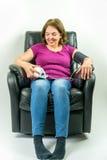 Милая женщина среднего возраста сидя вверх по праву в черном кожаном кресле recliner Проверять кровяное давление используя портат стоковое изображение