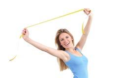 Милая женщина счастливая протягивающ ленту измерения стоковая фотография