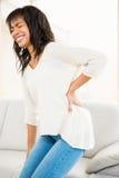 Милая женщина с болью в спине стоковые фотографии rf