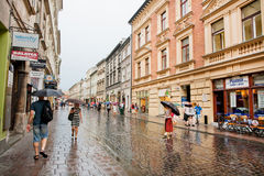 Милая женщина с зонтиком идя под дождь в старом городе домов Стоковые Изображения