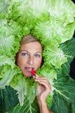 Милая женщина с листьями салата аранжировала вокруг ее головы есть r Стоковые Фото