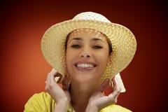Милая женщина с соломенной шляпой усмехаясь на камере Стоковое Изображение RF