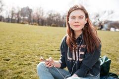 Милая женщина слушая к музыке от мобильного телефона на лужайке Стоковые Фотографии RF