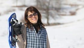 Милая женщина с snowshoes в горах Стоковая Фотография