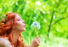 Милая женщина дуя на одуванчике Стоковое Изображение RF