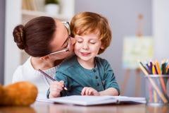 Милая женщина целуя ее сына Стоковое Фото