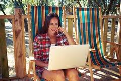 Милая загоренная женщина сидя с компьтер-книжкой на пляже chai лета Стоковое Изображение RF