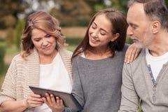 Милая зрелая семья наблюдает компьтер-книжку Стоковое Фото