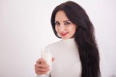 Милая здоровая женщина питьевое молоко от стекла изолированного на белой предпосылке Стоковые Изображения RF
