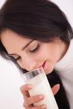 Милая здоровая женщина питьевое молоко от стекла изолированного на белой предпосылке Стоковая Фотография RF
