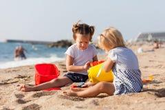Милая игра девушек на пляже Стоковая Фотография