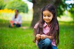 Милая испанская девушка в парке с матерью на предпосылке стоковые изображения rf