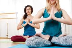 Милая йога практики девушки, размышляя и ослабляя в положении лотоса Стоковые Изображения RF
