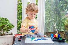 Милая картина мальчика с красочными красками стоковые фото