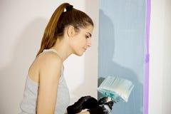 Милая картина молодой женщины восстанавливая домашний голубой цвет Стоковое Фото